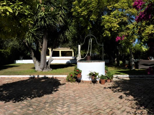 Casa Coria del Rio: large lush garden with pool and outdoor kitchen
